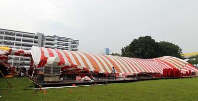 一阵强风骤雨袭过来,大如足球场的帐篷应声倒塌,造成一名妇女受伤。