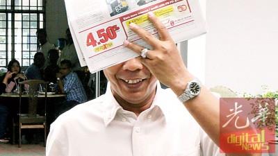 被告安林周二独自现身怡保反贪污法庭面对2起贪污提控,连为报纸遮脸。