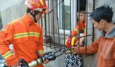 救期间,消防员为男童戴上头盔,以免被工具误伤。