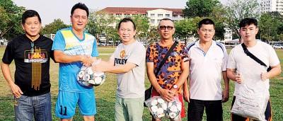 彭杯竞赛顾问林清吉(左3)移交赛会衣服和皮球给大马子民同少年联队代表。