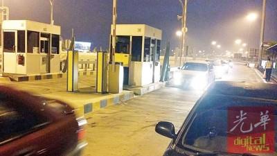 一名身上没有足够现金的车主,把车子(右)停在收费站旁等待电子收费系统修复。
