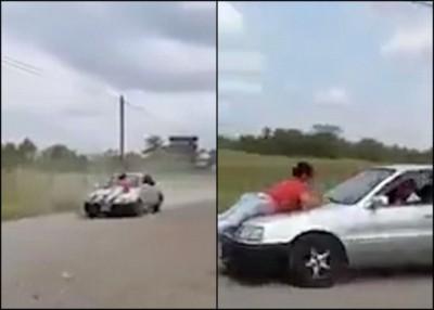 一名红衣女子被绑在车盖上。