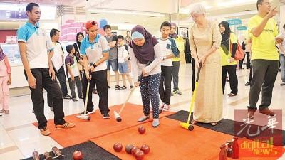 """章瑛与民众试着""""木球""""运动。"""