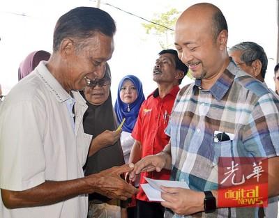慕克里(右)颁发援助品给予受惠者。