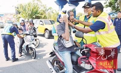 卡莱古玛(右起)及沙比里协助摩托骑士更换新头盔。