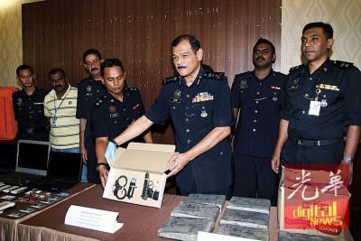 阿都哈密(右3)展示警方起获的气枪和手铐。