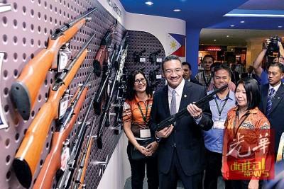 希山慕丁(左2)巡视菲律宾枪械展摊。