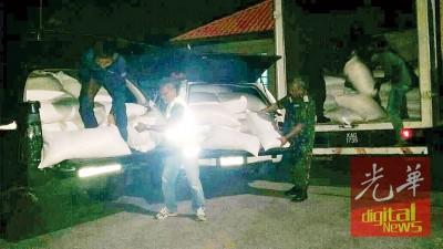 执法人员展示起获的走私白米。