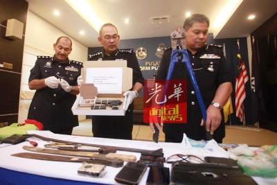 阿都嘉化连同槟刑事调查组主任拿督扎卡里亚(右一)及东北县警区主任米尔助理总监(左一)向媒体展示起获物品。