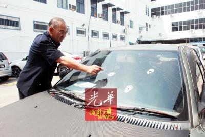 阿都嘉化指出警方击中的弹孔。
