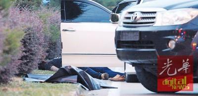 枪匪倒卧在路旁。