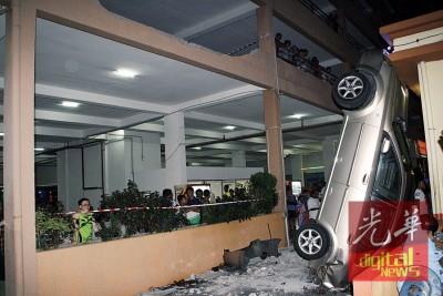 男子误踩油门,撞破二楼停车场围墙后摔下。