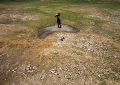 印度旱灾严重,一名小男孩在仅余的小水洼中洗澡。