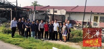黄东源(右4)与其团队在被大火烧成废墟的店屋前合照。