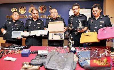 莫哈末阿南(中)由建功警官陪同,召开记者会,向媒体展示警方起获的赃物及匪徒的干案工具等。