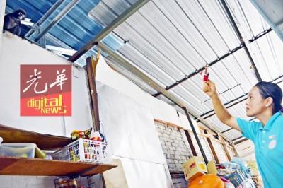 黑毛猴子每日早上在店后面的屋梁守着,等待李宜霖(右)给食物吃。