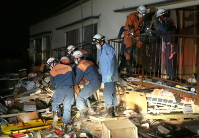 搜救人员从瓦砾堆中救出一名受困民众。(法新社照片)