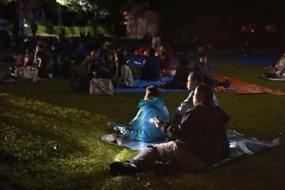 余震不断,居民夜宿草场。(法新社照片)