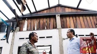 阿兹兰(右)巡视一里屋顶被风吹走之甘榜住屋,而慰问灾民。