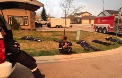 消防员连日救火,躺在草地上稍歇。