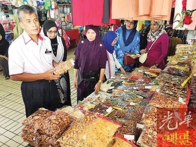 重新尼(左1)检查巴东无刹边境市集售卖的食品包装。