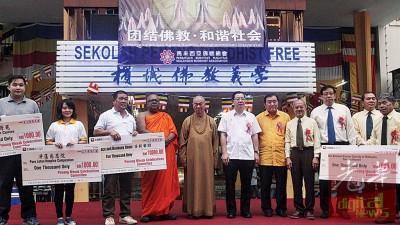 英达拉上那法师(左4)、天恒长老、林冠英、黄家泉、骆福汉与祝友成以及各级受惠团体代表合照。