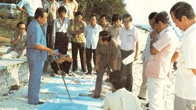 林苍祐在实地视察发展计划时,在海边沙滩上就地摊开地图向官员们作出指示。