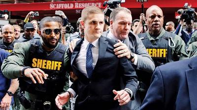 尼罗(中)在父亲(中右)和警方护送下离开法庭。