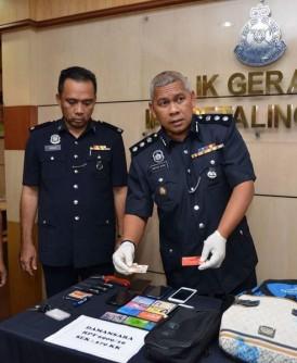 莫哈末扎尼(右)展示起获的贼赃。