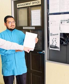 尤索夫(右起)手持报案纸,与黄健强指出遭破坏的管理层办公室玻璃窗。