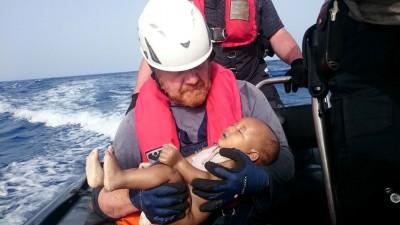 救援人员抱着已无体温的难民婴儿。(法新社照片)