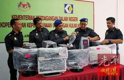 沙哈鲁丁(中)在执法人员陪同下,检查起获的电脑器材。