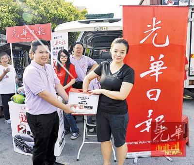本报发行部经理周志伟让签购的订户现场抽幸运奖赢名表环节。