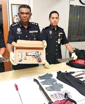 阿都阿兹(中)星期三在记者会出示警方起获的作案工具及手枪。