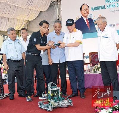 马迪乌士以吉北尤仑区科学嘉年华开幕仪式上操作小机器人,右一也上祖丁阿里,右三也奥士曼阿兹。