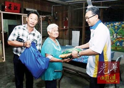 阿兹兰(右)分发援助品予玻州新程灾民,左1啊玻州新程村长林宥宇。