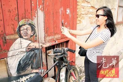 游客正拍下遭破坏的追风少年壁画。