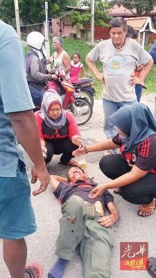 两名巫裔女子热心照顾伤者,并用手为伤者扇凉,场面温馨感人。