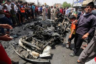民众围观萨德尔城汽车炸弹爆炸遗下的残骸。(法新社照片)