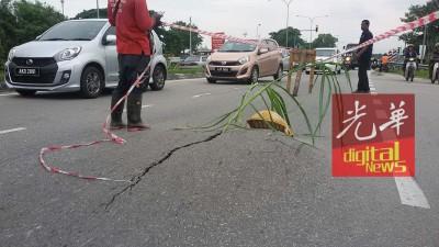 路人协助把爆开凸起如路峰的道路围起来,以免再有人受害。