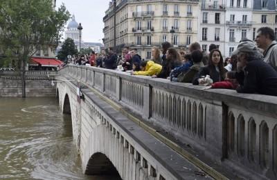 市民在桥上看泛滥的河里。(法新社照片)