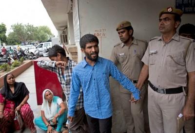 2名被告(中)在判刑后被带离法庭。