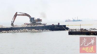 承包商开始向海堆石,拓展保护海岸边缘地带的护坡工程。