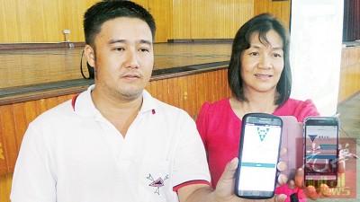 胡进和(左)与校长李思蓓展示SIS系统手机界面。