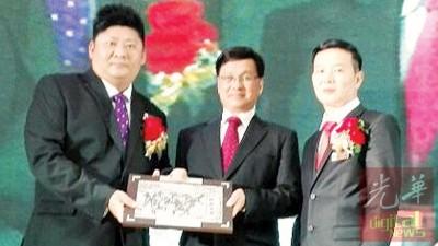 方天兴(中)从张赈琮手中接过纪念品。右为胡荣兴。