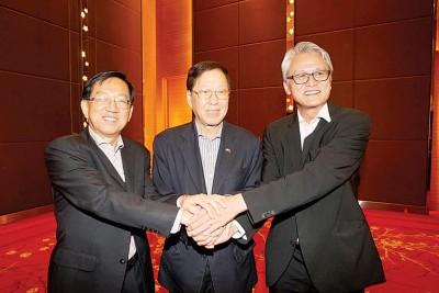 两位总会长候选人,陈友信(左)和刘俊光(右)与原任总会长黄汉良(中)握手言欢。