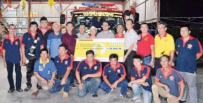 杨筌贵(后排右4)移交模拟支票给鱼池区自愿消防队,作为添购消防车基金,盼能抛砖引玉。