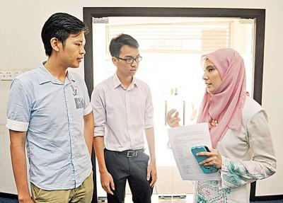 努鲁(右)向两位学生代表了解国外深造的奖学金申请的情况。左起为翁尼克和贾斯丁杰森。