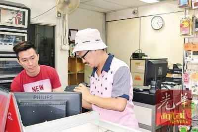 邱志鸿(右)一出院就回到店里处理事务。