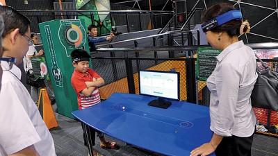 周玉清与其子在斗脑意念,比赛谁能推动桌上的圆球。